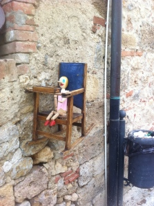 A beautiful medieval town with cobblestone, old shops, beautiful architecture, and this creepy thing.