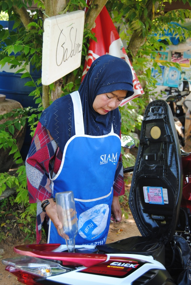 Adorable muslim woman refueling our scooter.